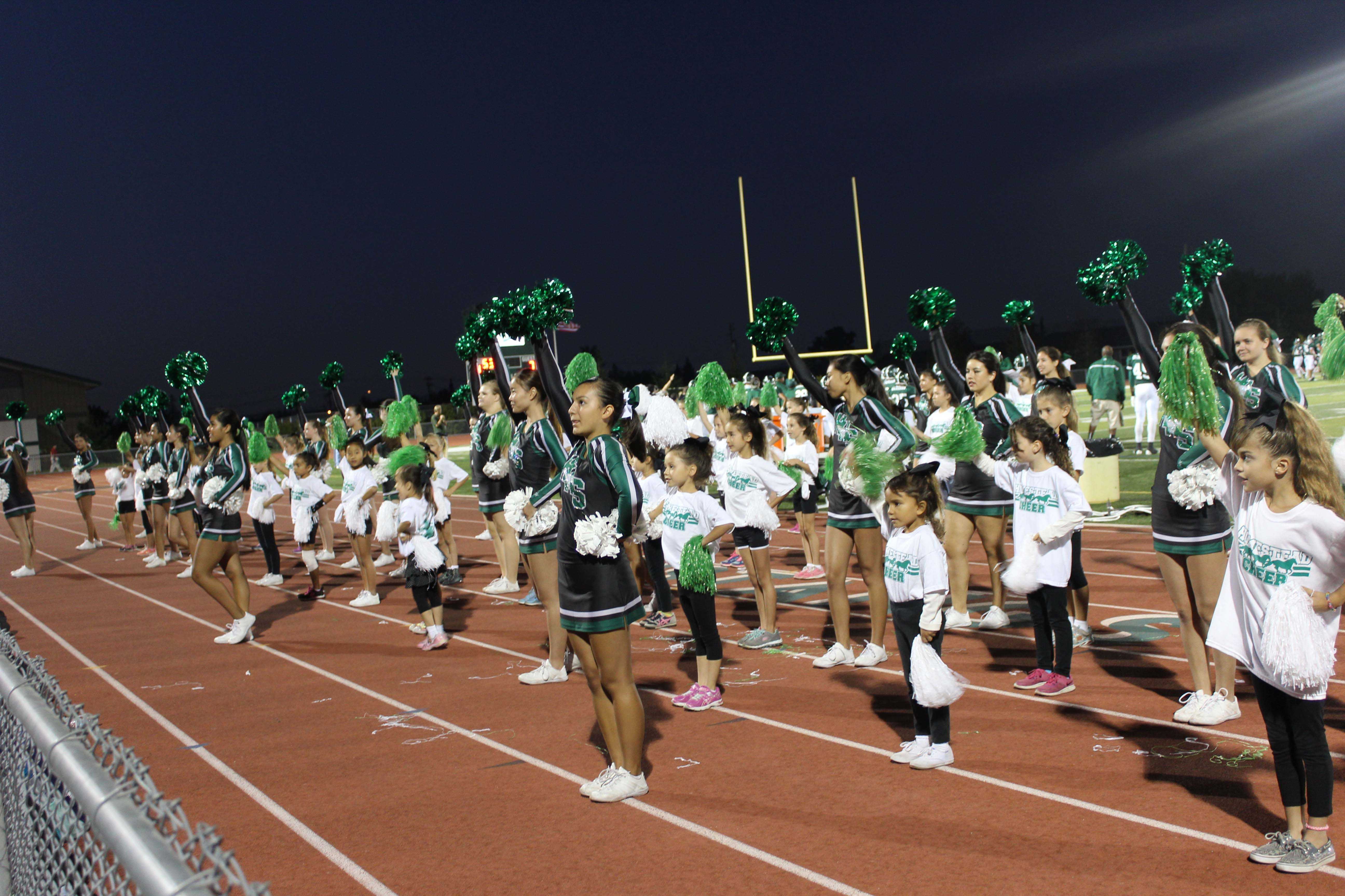 Campers join the Cheer team in leading the crowd at the Homestead vs. Leland football game last Friday.