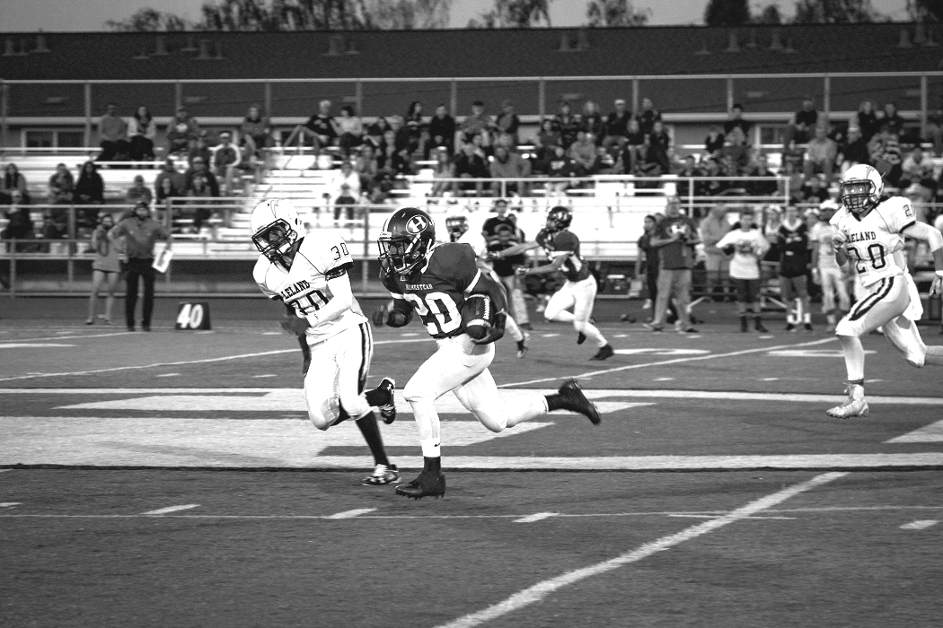 Ward rushes the ball through the Leland High School defense, Sept. 2