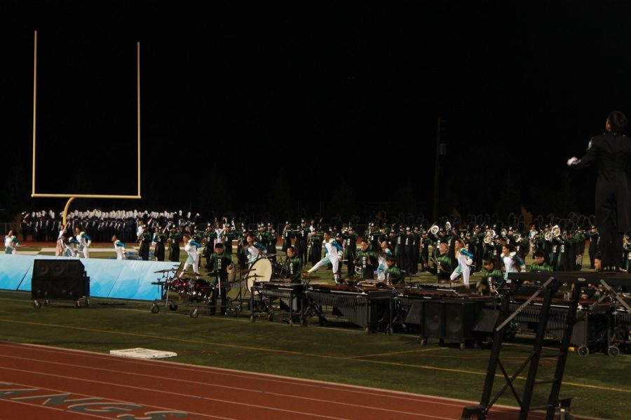 On+the+night+of+Marching+Band+EXPO%2C+members+are+in+full+action+on+the+field+during+their+performance.