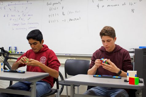 Samrudh Shenoy (11) and Lior Kishinevsky (12) focus on solving Rubik's Cubes and compete for the shortest solve time.