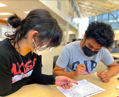 Junior tutor Claire Oh helps junior tutee Aashish Dhungana with math homework.